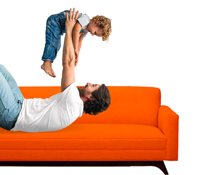 A man on a sofa playfully lifts up a smiling child