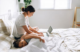 mother on laptop as child sleeps
